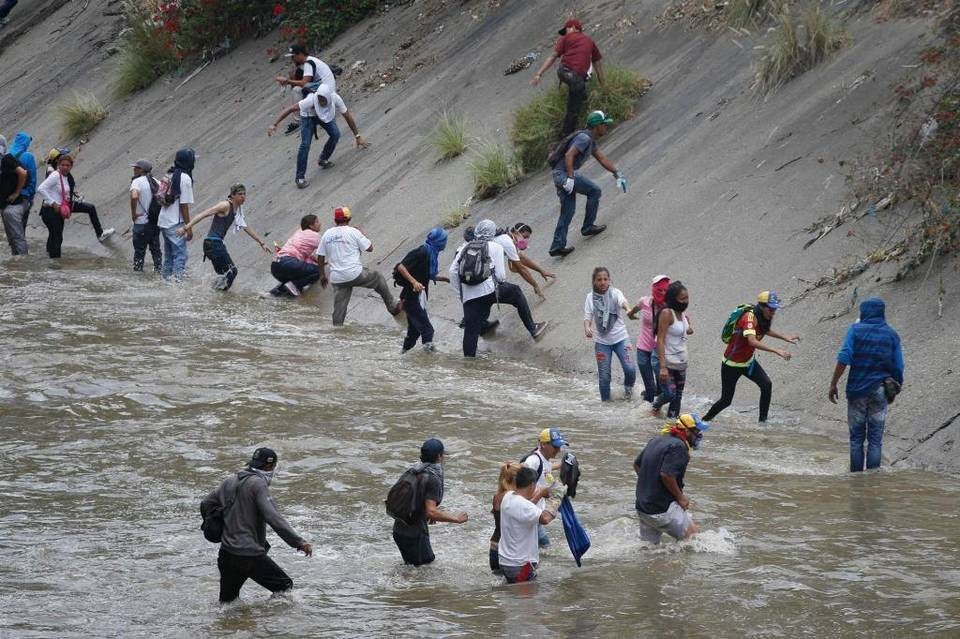 Demonstrators wade across the Guaire River as they run away from security forces during anti-government protests in Caracas, Venezuela, Wednesday, April 19, 2017. Tens of thousands of opponents of President Nicolas Maduro flooded the streets of Caracas in what's been dubbed the
