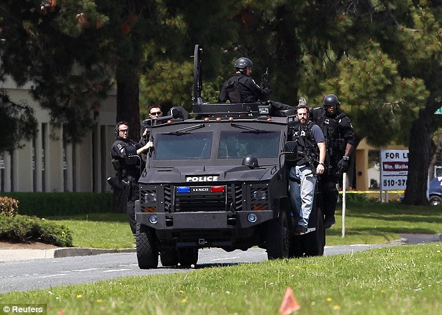 Hunt: Police arrive in an armoured vehicle after a gunman opened fire killing seven at Oikos University yesterday