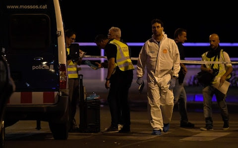 Policemen check the area after police killed five attackers in Cambrils near Tarragona