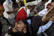 Anti-government protestors carry a wounded protestor from the site of clashes with security forces, in Sanaa, Yemen, Sunday, Sept. 18, 2011. Yemeni government forces opened fire with anti-aircraft guns and automatic weapons on tens of thousands of anti-government protesters in the capital pushing for ouster of longtime ruler Ali Abdullah Saleh, killing several people and wounding dozens.(AP Photo/Hani Mohammed)