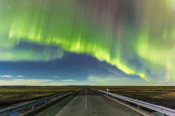 Aurora Borealis over a road near Vik in Southern Iceland.
