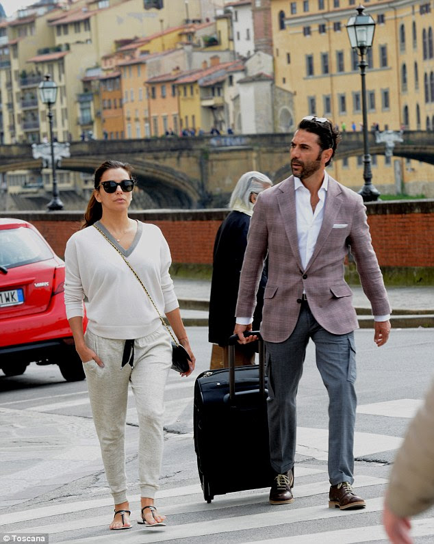 Chic couple: Eva was casual but chic in a white v-neck sweater and loose fit trousers for the trip to Italy