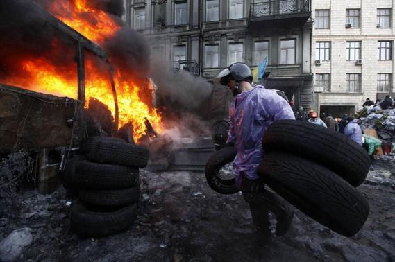An anti-government protester carries tyres at a barricade at the site of clashes with riot police in Kiev January 25, 2014. REUTERS-Vasily Fedosenko