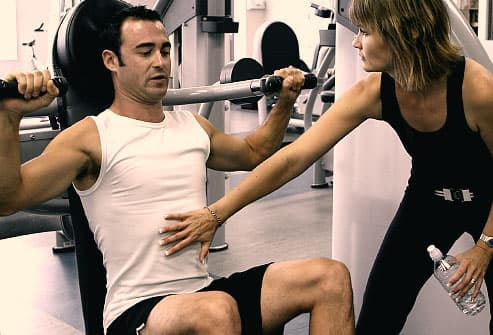Man using weigh machine with personal trainer