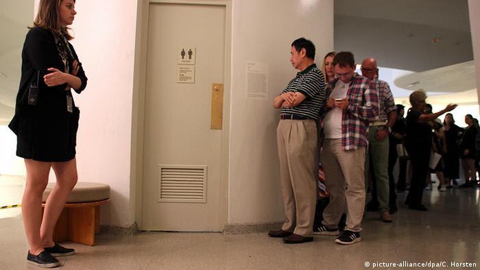 Im Guggenheim-Museum warten Kunstinteressierte vor der Toilette America aus Gold von Maurizio Cattelan (foto: dpa)