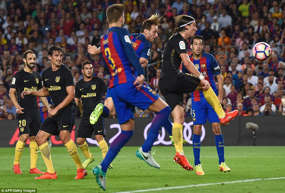 Barcelona's midfielder Ivan Rakitic  heads the ball into the net to score his side's opening goal against Atletico Madrid