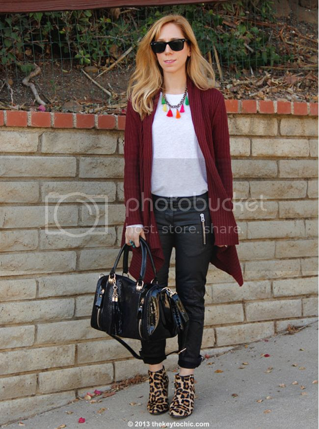 L.A. fashion blogger The Key To Chic wears an Isabel Marant for H&M white T-shirt and black waxed biker jeans with a Mellow World handbag, Charlotte Russe oxblood waterfall cardigan, and Topshop leopard boots