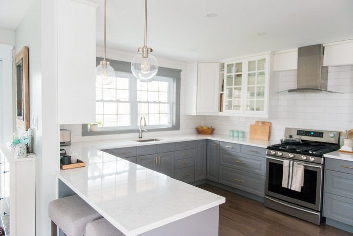A gray and white kitchen makeover using IKEA cabinetry quartz countertops subway tile and gold hardware