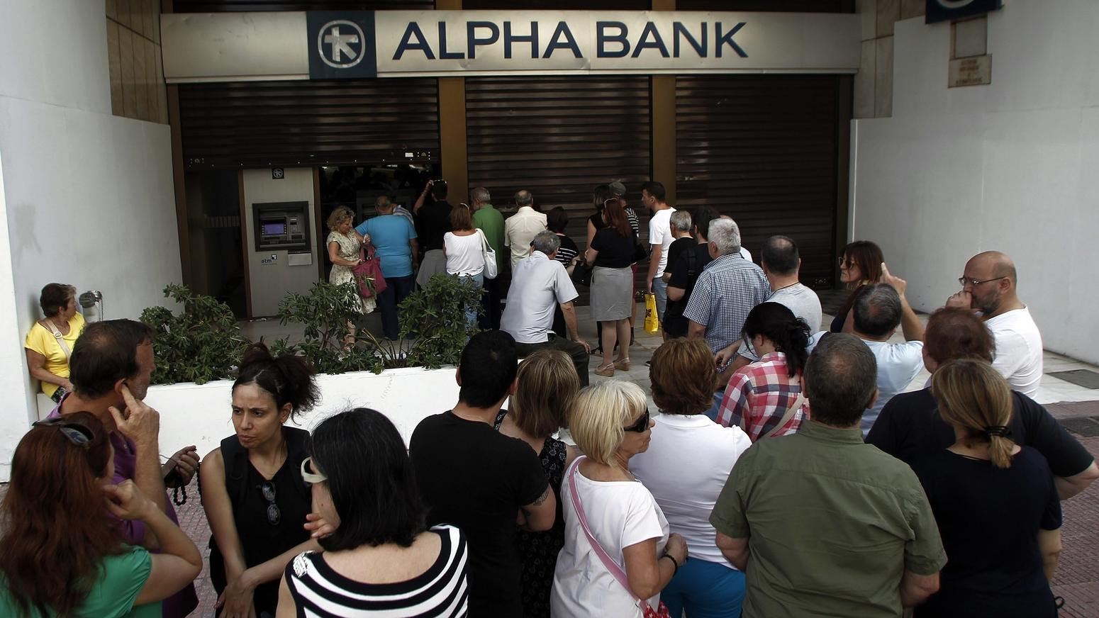 People withdraw money from ATM of Greek Alpha Bank