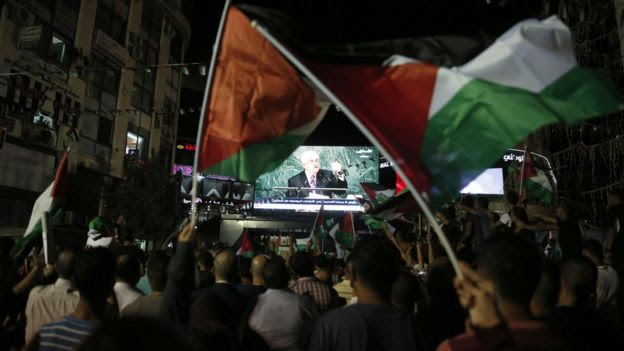 Palestinians watch Mahmoud Abbas address the UN General Assembly on a big screen in Ramallah (30 September 2015)