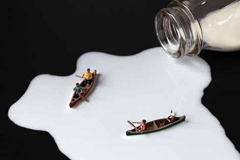 Humorous photographs of miniature figurines on food,