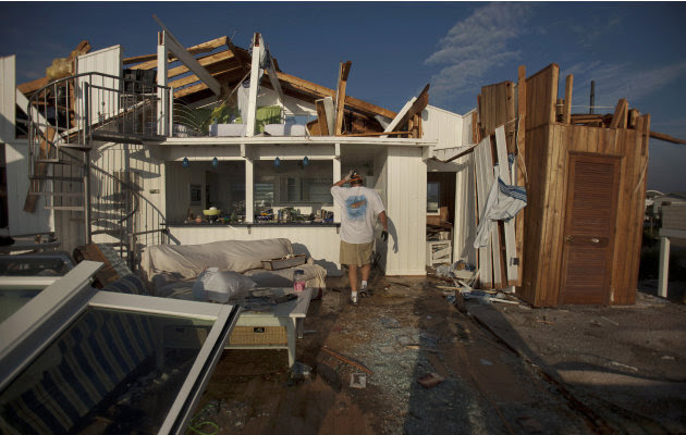 Casey Robinson, and his wife Denise Robinson clean up what is left of their beach house after Hurricane Irene passed Sunday, Aug. 28, 2011 in Virginia Beach, Va. (AP Photo/The Virginian-Pilot,  L. Tod