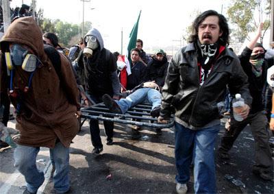 Varios manifestantes trasladan a un herido. -