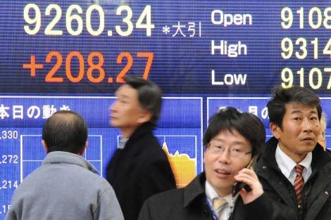 Ejecutivos que caminan frente a los resultados del índice Nikkei en Tokio.| Efe | Everett Kennedy