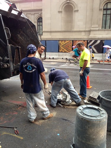 Garbagemen removing a large piece of crumpled metal, UES