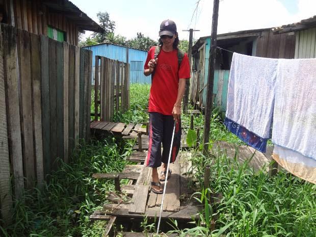 Ao sair de casa, no bairro da Cabanagem, Pedro Michel enfrenta uma trilha de obstáculos: palafitas, terreno instável e lixo. (Foto: Luana Laboissiere/G1)