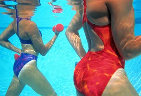 Mulheres que fazem hidroginástica com halteres
