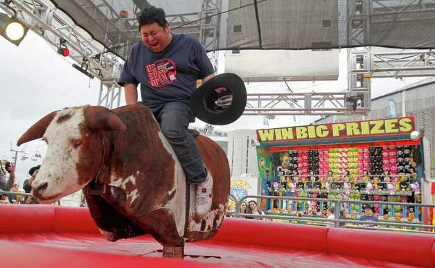 """Japanese Sumo wrestler Takuji Noro who competes as """"Noro"""" rides a mechanical bull during a tour of The Houston Livestock Show & Rodeo Wednesday, March 7, 2012, in Houston. Photo: James Nielsen, Chronicle / © 2011 Houston Chronicle"""