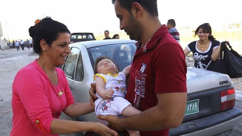 Une famille de chrétiens ayant fui Mossoul arrive à Qaraqosh dans le Kurdistan le 19 juillet 2014. Située dans la province de Ninive, cette ville chrétienne est considérée comme sûre.
