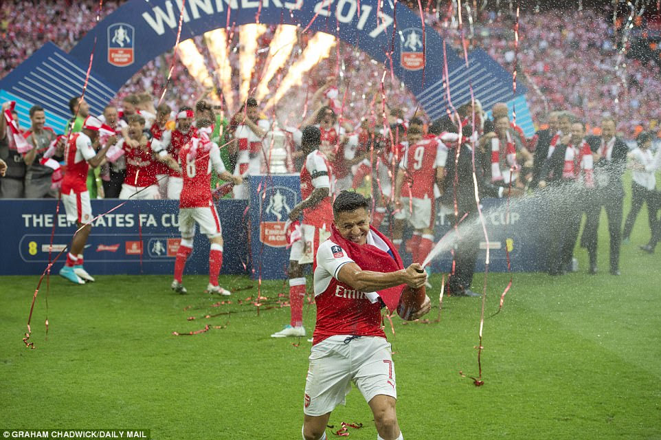 Sanchez sprays champagne at the photographers as his team-mates jump around behind him on the pitch