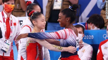 Biles y Guan se abrazan durante la final de la barra de equilibrio.