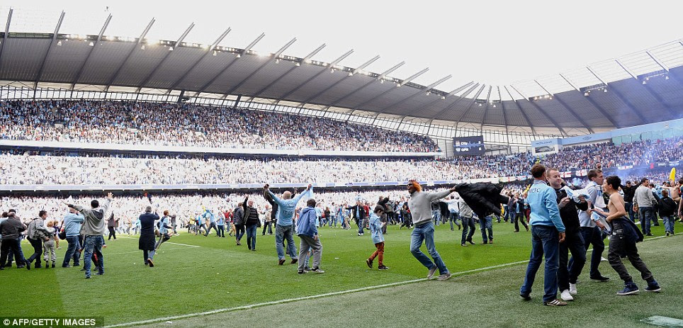 Our moment: City supporters pour on to the pitch at the final whistle at the Etihad Stadium