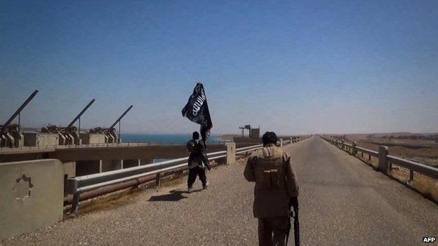 Image allegedly showing Islamic State militants waving the trademark Jihadist flag as they inspect the grounds of the Mosul dam (9 August 2014)