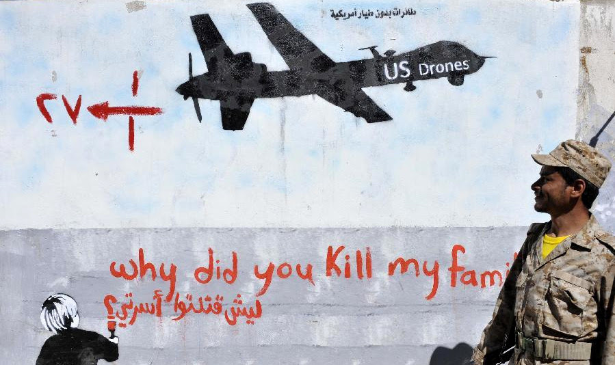 A Yemeni soldier looks at the graffiti of U.S. drone strike painted on a wall as a protest against the drone strikes, in Sanaa, Yemen, on Dec. 21, 2013. (Photo: Mohammed Mohammed/Xinhua)