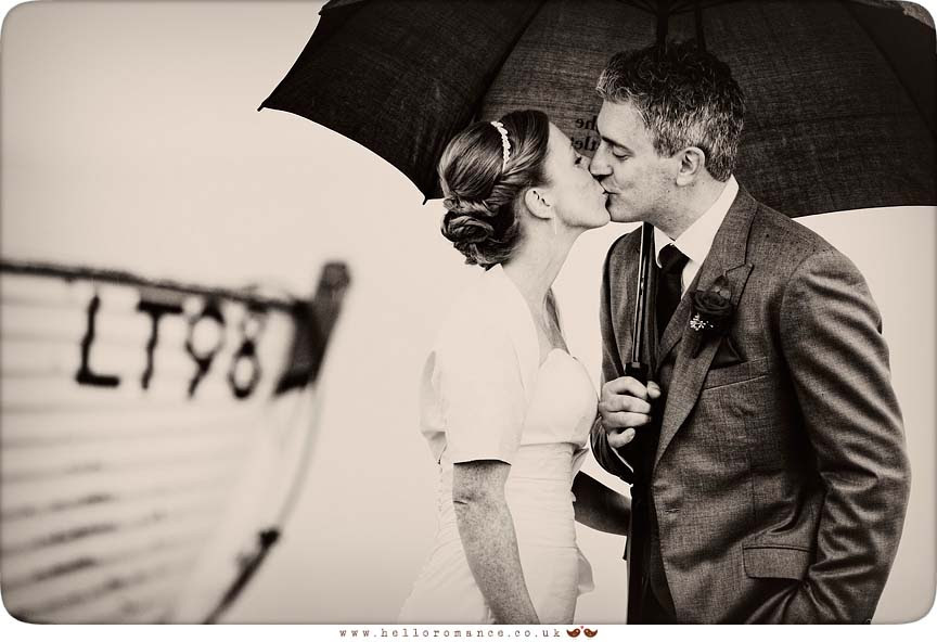 Bride and Groom kissing in rain on Dunwich Beach with umbrella - Westleton Crown Wedding Photography - Kate and Rob - Hello Romance Wedding Photography Suffolk