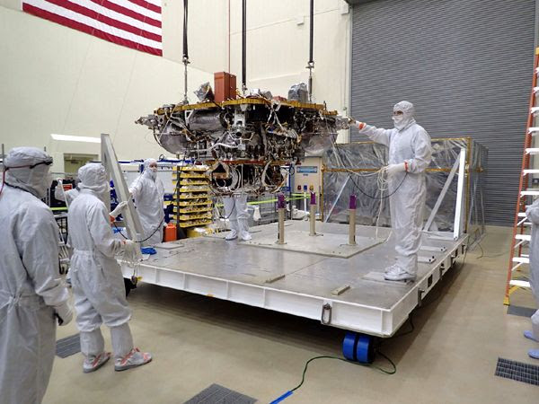 Lockheed Martin engineers take the InSight Mars lander out of temporary storage in June of 2017...to begin testing the spacecraft prior to its launch in May of 2018.