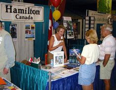 Sarasota Sister Cities Director of relations with our twinned city of Hamilton, Ontario Carol Furlong greets visitors at the Hamilton booth at the Hands of Heritage Fest at Sarasota's Robarts Arena in 2003,