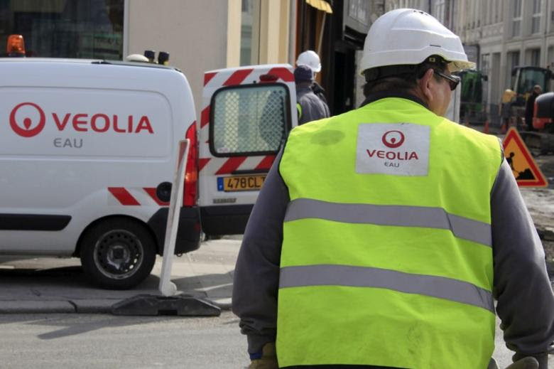 FILE PHOTO -  A worker of Veolia Water pushes a barrow during roadworks in the street in Cambrai, northern France, March 21, 2013.   REUTERS/Pascal Rossignol/File Photo