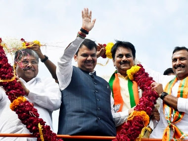 Devendra Fadanvis waves at his supporters during the 'Janadesh Yatra', in Pune. PTI