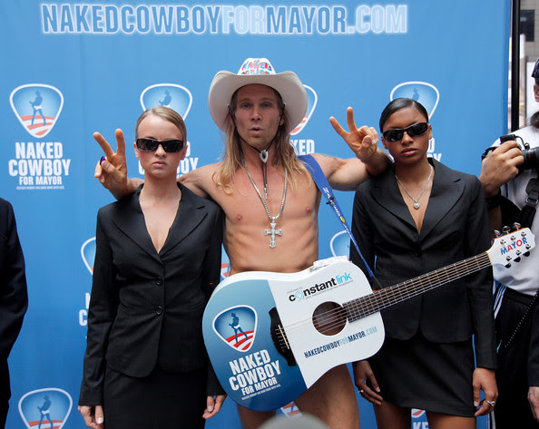 """Actor/ local New  York personality Robert John Burck (C) also known as """"The Naked Cowboy"""" poses with his security detail following a press conference announcing the launch the Naked Cowboy's New York City mayoral campaign at Military Island, Times Square on July 22, 2009 in New York City."""