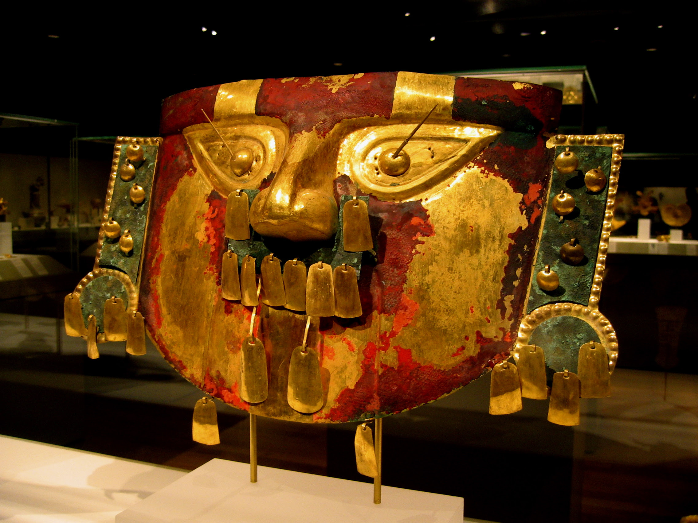 Funerary Mask, 9th-11th century Peru; (Lambayeque) Hammered gold with cinnabar and copper overlays, cinnabar; H. 11 1/2 in. (29.2 cm) Gift and Bequest of Alice K. Bache, 1974, 1977 (1974.271.35) (Wikimedia Commons)