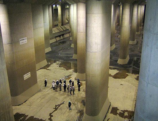 "Visitantes observam gigantesco tanque d´água ""Templo Subterrâneo"", entre seus pilares de concreto"
