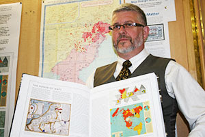 Professor Peter Vujakovic with the Times Atlas.  Image Courtesy of Phys.org.