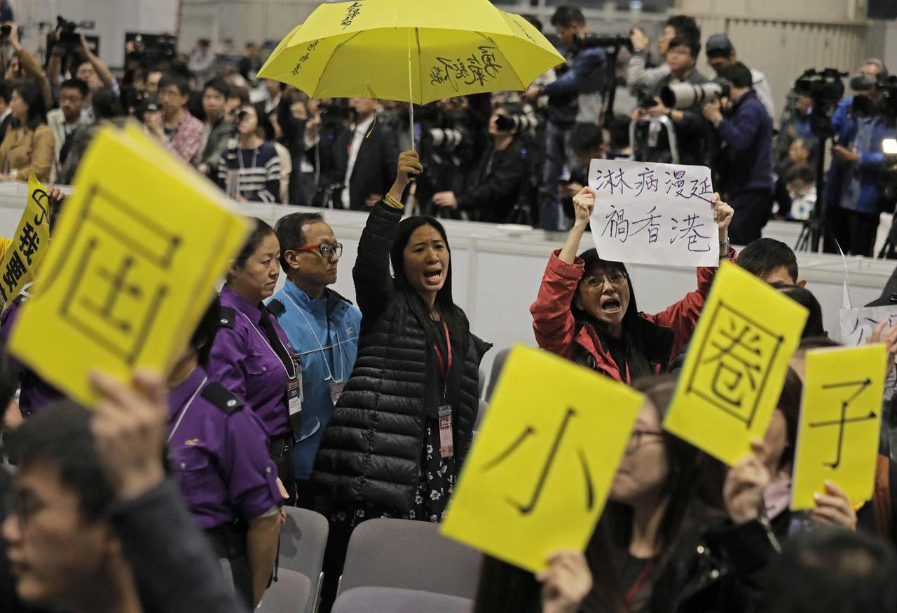Protesters raise an yellow umbrella and placards to protest against former Hong Kong Chief Secretary Carrie Lam after she declared her victory in the chief executive election of Hong Kong in Hong Kong, Sunday, March 26, 2017. A committee dominated by pro-Beijing elites chose Hong Kong's next leader Sunday in the first vote since huge pro-democracy protests erupted over the election system in 2014. Lam, the government's former No. 2 official and Beijing's favored candidate, received 777 votes and will become the first female leader for the city and its fourth since British colonial control ended in 1997.