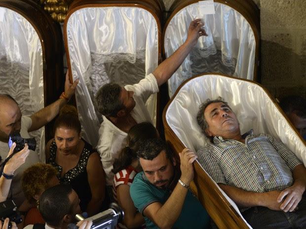 Homem é carregado por seus parentes durante a Procissão das Mortalhas, em Santa Marta de Ribarteme, na Espanha, na quarta (29) (Foto: AFP Photo/Miguel Riopa)