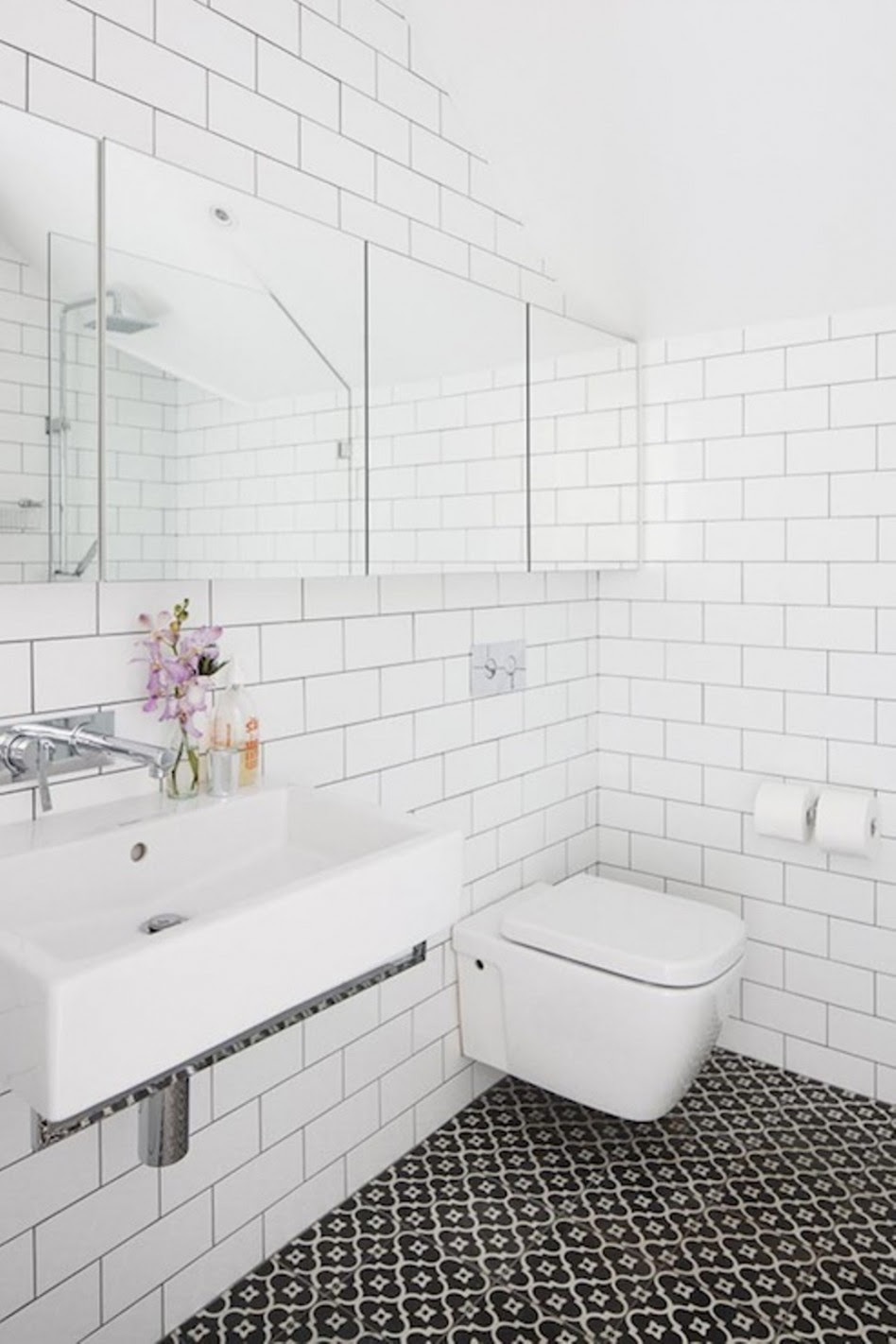 pure white subway tile for bathroom walls huge wide frameless mirror luxurious white sink double stainless steel faucets artistic glass vase beautiful flowers range white modern toilet
