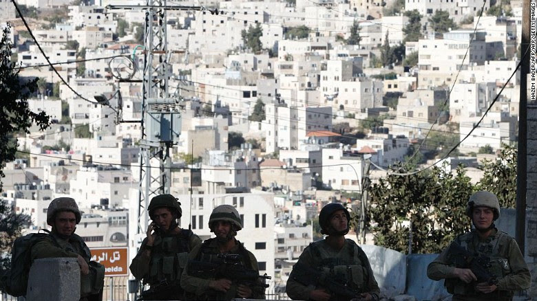 Israeli soldiers stand guard blocking an entrance to the Jewish settlers zone of Hebron's Tel Rumeida neighbourhood, on September 18, 2016.