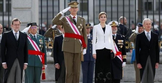 Los reyes, junto al presidente del Gobierno, Mariano Rajoy (i), y el ministro de Defensa, Pedro Morenés (d), escuchan el himno nacional durante la celebración de la Pascua Militar, a la que asisten representantes de las instituciones del Estado, los tres