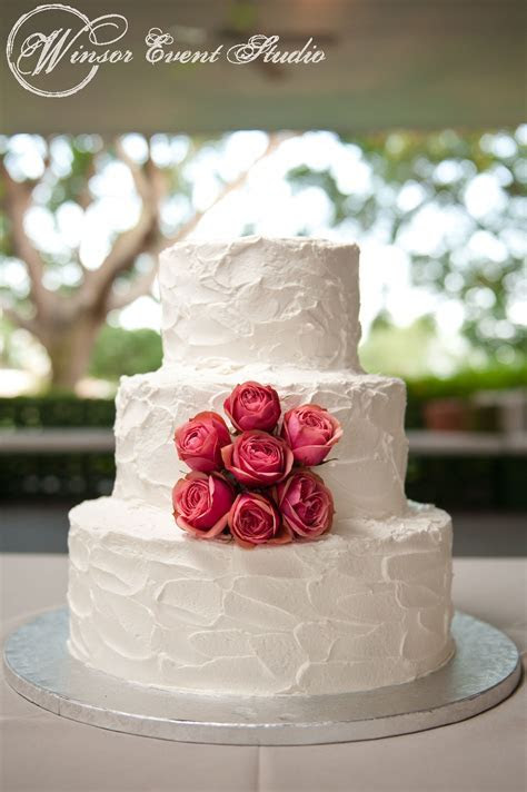 Simple buttercream wedding cake with coral spray roses