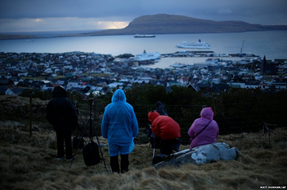 People wait for the start of a total solar eclipse in Torshavn, the capital city of the Faroe Islands