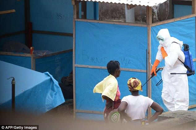 O surto de Ebola na África Ocidental tem acelerado rapidamente com quase 1.000 mortes no mês passado, de acordo com os últimos dados da OMS. Acima, as mulheres que se acredita estarem contaminados com Ebola olhar enquanto um trabalhador exerce pulverização em Monrovia