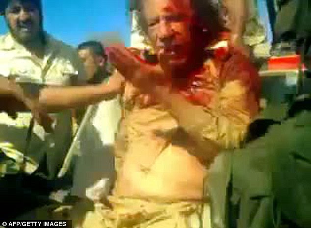Gaddafi lifts a hand to his face to see the blood pouring from his wounds. The mobile phone footage shows the dictator slumped against a jeep but still alive