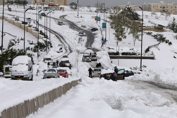 Vehicles are see stranded in the snow in Jerusalem on December 13, 2013. AFP PHOTO/AHMAD GHARABLI