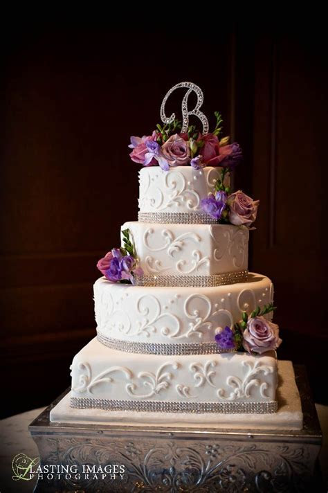 Four tier round, square and hexagon shaped cake with