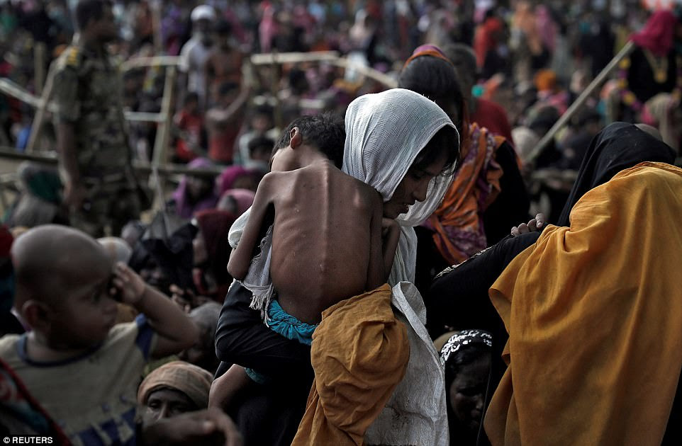 A woman carries her ill child in a refugee camp at Cox's Bazar, Bangladesh, September 26, where Rohingya refugees have settled after fleeing persecution from the government in Myanmar, where the minority Muslims are seen as illegal immigrants by some Buddhists