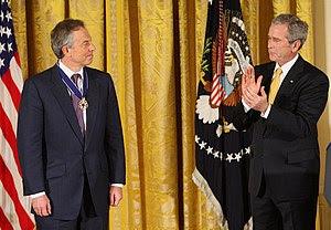 English: President George W. Bush applauds for...